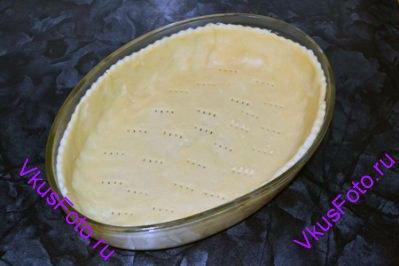 Готовое песочное тесто раскатать и выложить в жаропрочную форму с высокими бортами. Дно пирога проколоть вилкой.
