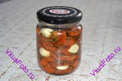 Готовые остывшие помидоры уложить в банку вместе с дольками чеснока и залить маслом. Хранить в холодильнике до 2-х месяцев.