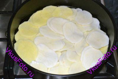 Разъемную форму смазать маслом и выложить 1/3 часть картофеля.