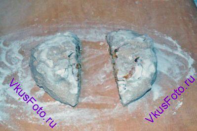 Поднявшееся тесто выложить на доску с мукой. Разрезать на 2 равные части.