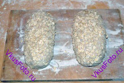 Смазать поверхность хлеба водой и обмакнуть в овсяные хлопья. Поставить в теплое место на 45 минут.