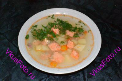 Положить в суп форель и картофель. После того как вода закипит, варить 10-15 минут. Подавать, посыпав нарезанной зеленью.