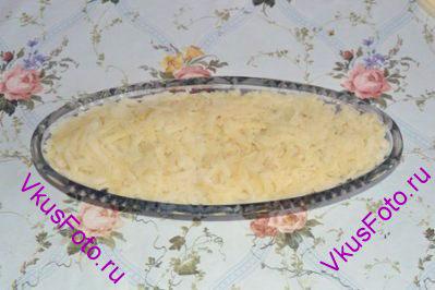 Картофель натереть на крупной терке. Разложить ровным слоем и утрамбовать ложкой.