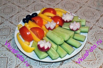 <i>Выбор продуктов для овощной нарезки может быть любой.</i> <br /><br /> У огурцов удалить кончики, разрезать поперек на 2-3 части (в зависимости от длины огурца). И каждую часть разрезать на четвертинки. <br /> У перца удалить семена и перегородки. Нарезать соломкой. <br /> Помидоры нарезать на четвертинки. <br /> Разложить овощи на тарелке. Украсить маслинами и редисом нарезанным в форме цветка.