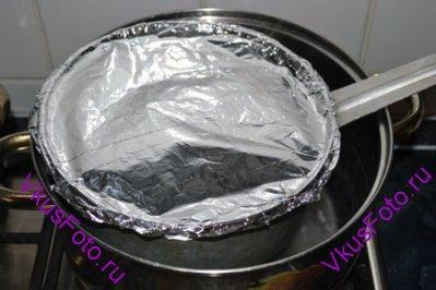 Верх дуршлага закрыть фольгой и установить в кастрюлю с кипящей водой так, чтобы рис продолжал вариться на пару около 10 минут.