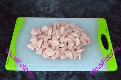 Сосиски очистить от оболочки и нарезать кусочками.