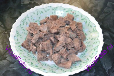 Из бульона вынуть мясо и нарезать на кусочки.