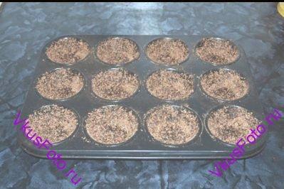 Формы для пудингов смазать маслом и посыпать шоколадной крошкой. Лишнее стряхнуть.