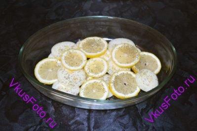 На дно жаропрочной посуды разложить ломтики лимона и лук нарезанный кружочками. Посыпать солью и розмарином.