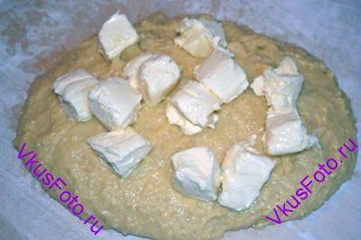 Переложить тесто на доску (без муки) и замесить тесто руками. Тесто будет мягкое и липкое. Когда тесто станет однородным, добавить масло нарезанное на кусочки.