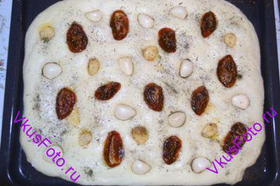Разложить на поверхности теста вяленые помидоры, чеснок и вдавить их в тесто. Посыпать фокаччу сушеным базиликом. Поставить в теплое место на 50 минут.