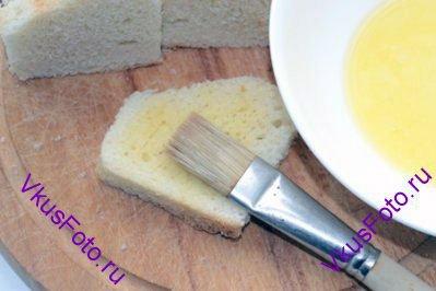 Разрезать ломтики батона пополам и смазать растопленным сливочным маслом.