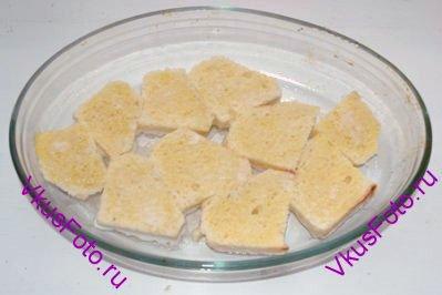 Форму для выпечки смазать маслом. Обмакнуть каждый ломтик в молочно-яичную смесь и уложить на дно формы.