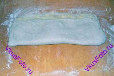 Поверхность теста смазать водой и обсыпать кукурузной мукой. Сложить тесто вдоль, оставляя 3 см до края.