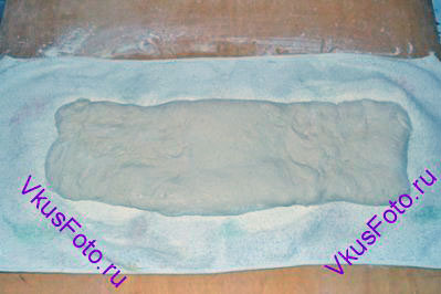 Переложить тесто на полотенце посыпанное мукой. Переложить на него тесто швом вниз.