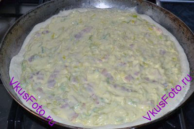 Тесто раскатать, уложить на сковороду и проткнуть вилкой в нескольких местах. Распределить начинку по поверхности теста, оставляя края.