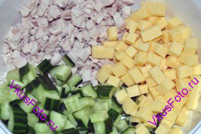 Соединить в салатнике курицу, сыр и огурцы.