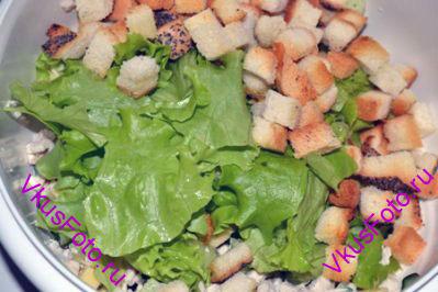 Добавить сухарики и листья салата.