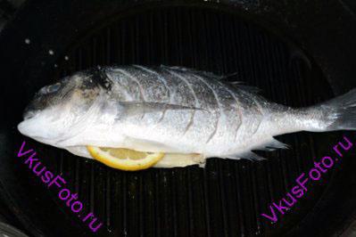 Натереть рыбу солью и перцем снаружи и внутри. В брюшко положить ломтик лимона. На сковороде-гриль разогреть масло и положить рыбу. Жарить 10 минут.