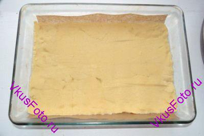 2/3 части теста раскатать по размеру формы (20х30 см). выложить в форму выстланную бумагой для выпечки. Если раскатать тесто не получается, то нужно выложить кусочки теста в форму и прижать пальцами, создавая корж.