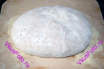 Поднявшееся тесто выложить на доску и снова <a href=http://www.vkusfoto.ru/raznoe/kak_sformirovat_shar_iz_testa/116.html>сформировать шар</a>.  Доску с хлебом поставить в теплое место.