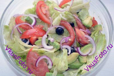 В салатник добавить листья салата. Залить заправкой и перемешать.
