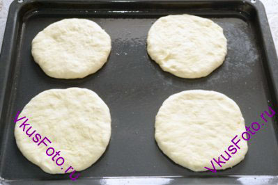Шарики раскатать в лепешки толщиной 1 см, диаметром примерно 12 см. И разложить на противень смазанный маслом.