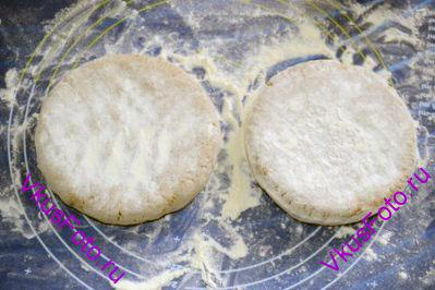 Тесту придать форму лепешек толщиной 2 см и обильно обсыпать пшеничной мукой.