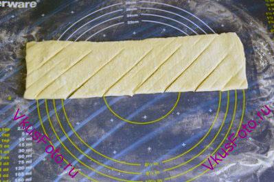 Сложить тесто вдоль пополам и сделать косые надрезы, не доходя да края 2-2,5 см.