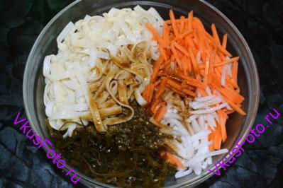 В салатницу положить лапшу, дайкон, морковь и морские водоросли. Залить соусом и заправить кунжутным маслом.