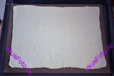Половину теста раскатать в большой прямоугольник и положить на противень с пекарской бумагой.