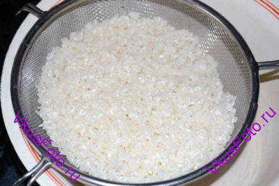 Рис промывать холодной водой до тех пор, пока вода не станет прозрачной. Откинуть рис на сито и оставить на 1 час.