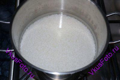Рис положить в кастрюлю и залить водой из расчета 125 мл воды на 100 г риса.