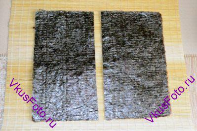 Листья Нори разрезать поперек на 2 части.