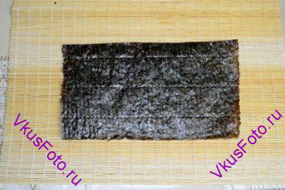 На циновку положить горизонтально разрезанный лист Нори.