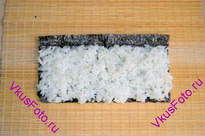 Положить на лист Нори готовый и приправленный рис, оставляя не заполненными верхние 1,5 см листа.