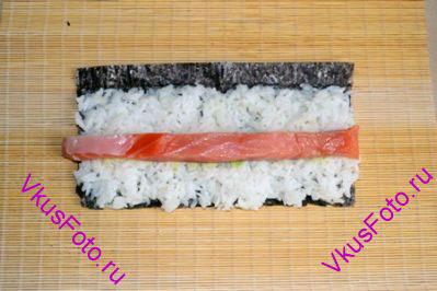 Уложить на васаби рыбу нарезанную длинным бруском.