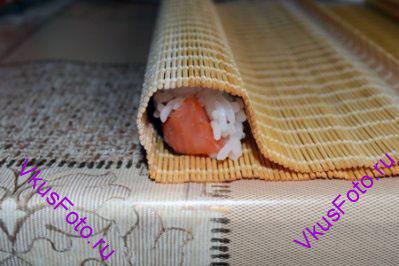 Начать заворачивать ролл с помощью циновки. При этом нижний край нужно состыковать с верхним краем, где заканчивается рис.