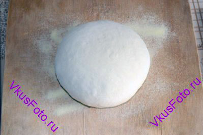 Из поднявшегося теста <a href=http://www.vkusfoto.ru/raznoe/kak_sformirovat_shar_iz_testa/116.html>сформировать шар</a> и положить на доску присыпанную мукой или манкой. Поставить в теплое место на 30 минут.