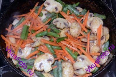 На сковороде где жарилось мясо, обжарить до полуготовности грибы, морковь, зеленую фасоль. Примерно 10-15 минут.