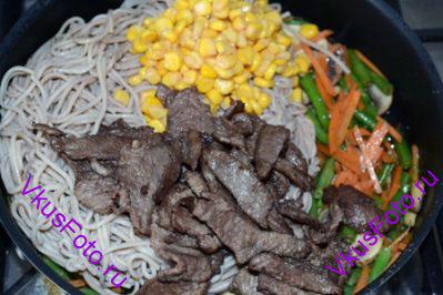К овощам добавить гречневую лапшу, кукурузу и мясо. Залить соусом и тушить до готовности овощей.