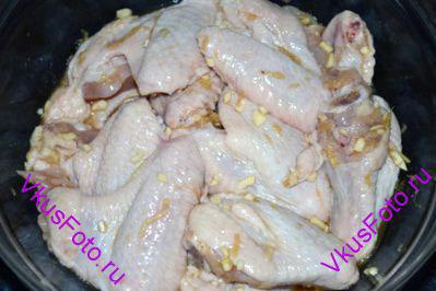 Куриные крылышки залить маринадом. Перемешать, чтобы все крылышки покрылись маринадом и поставить в холодильник на 4 часа.