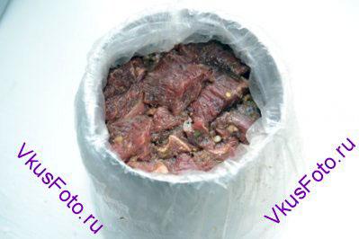 Ветчинницу выложить изнутри полиэтиленовым пакетом. Внутрь пакета, утрамбовывая, уложить кусочки мяса.