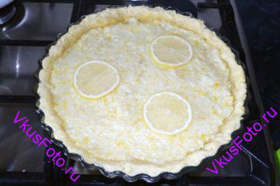 Затем вынуть форму из духовки убрать бумагу и горох. На полуготовый корж выложить начинку и разровнять. Украсить дольками лимона.