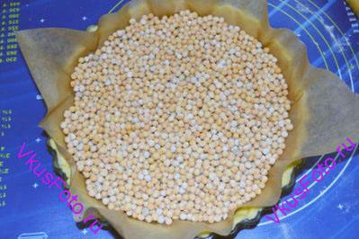 На корж положить пекарскую бумагу и насыпать сухой горох или фасоль. Для того чтобы при выпечке корж не вздулся. Поставить форму в духовку на 15 минут при температуре 190 градусов.