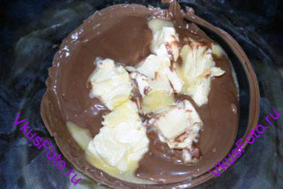 В шоколад положить сливочное масло порезанное на кусочки и размешать.