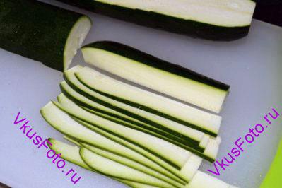 Цуккини разрезать сначала вдоль и затем поперек. Получится 4 части. Каждую часть нарезать длинными тонкими ломтиками, 2-3 мм толщиной.