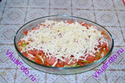 Сыр натереть на крупной терке и посыпать им овощи.