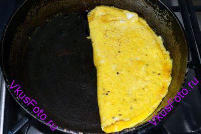При помощи лопатки сложить яичницу пополам.