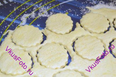 На доску тонким слоем посыпать сахар, сверху положить тесто и раскатать пласт толщиной 0,5 см. С помощью формочки вырезать печенья. При выпечке печенье уменьшается в размере, поэтому формочку лучше взять большого размера.